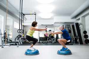 Beautiful fit senior couple in gym working out with weights and squatting at the same time
