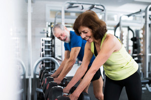 Beautiful fit senior couple in gym working out with weights