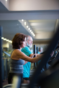 Beautiful fit senior couple in sports clothing in gym doing cardio workout, exercising on elliptical trainer machine. Sport fitness and healthy lifestyle concept.