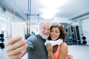 Beautiful fit senior couple in sports clothing in gym resting, taking selfie with smart phone