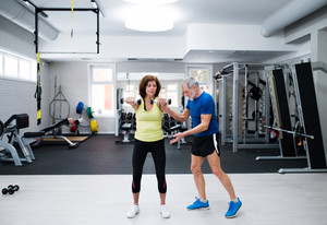 Beautiful fit senior couple in sports clothing in gym working out with weights, husband instructing his wife