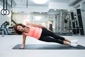 Beautiful fit senior woman in gym in sports clothing working her abs, doing side plank.