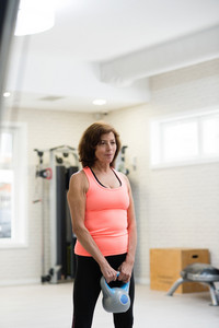 Beautiful fit senior woman in gym working out using kettlebells. Sport, fitness and healthy lifestyle concept.