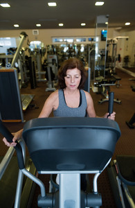 Beautiful fit senior woman in sports clothing in gym doing cardio workout, exercising on elliptical trainer machine. Sport fitness and healthy lifestyle concept.
