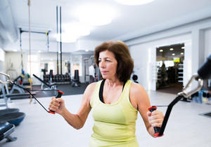 Beautiful fit senior woman in sports clothing in gym working out with resistance bands.
