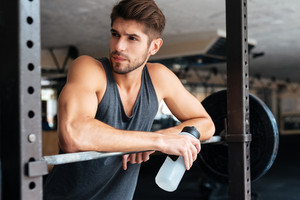 Beautiful fitness man with weights looking away. with bottle