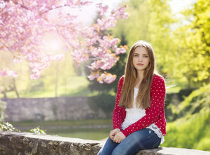 Beautiful girl in red cardigan sitting on a wall in spring garden with blooming trees