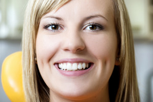 Beautiful girl is showing her white teeth at dentist