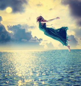 Beautiful girl jumping into the blue night sky over the ocean