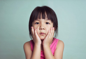 Beautiful girl looking sad with pouted lips. Closeup portrait of cute asian kid .