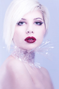Beautiful girl model with plastic around her neck. Cold toned and professional makeup.