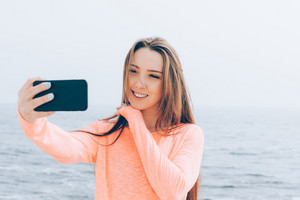 Beautiful girl with long brown hair takes pictures of herself on the phone at the beach. Portrait of a smiling woman against the sea.