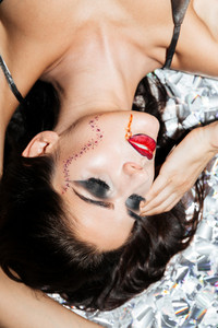 Beautiful gothic young woman with halloween makeup lying on sparkling background