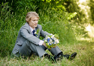 Beautiful groom is waiting for his bride on the meadow