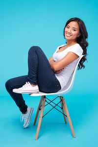 Beautiful happy asian woman sitting on a chair isolated on a blue background