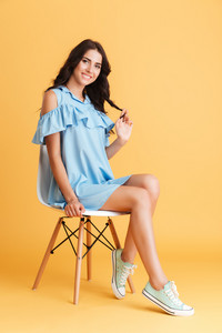 Beautiful happy brunette woman in blue dress posing on the chair isolated on a orange background
