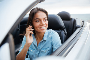 Beautiful happy woman driving car and talking on mobile phone