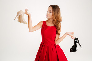 Beautiful happy woman holding high heels shoes isolated on a white background