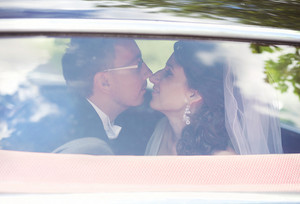 Beautiful happy young bride and groom kissing in retro car