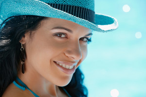 Beautiful happy young hispanic woman in straw hat smiling and relaxing near hotel pool. Horizontal shape, head and shoulders, copy space