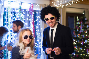 Beautiful hipster friends with sunglasses, wig and feather boa celebrating the end of the year, having party on New Years Eve, dancing, chain of lights and Christmas tree behind them.