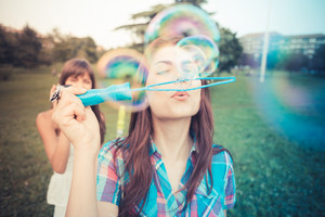 beautiful hipster young women sisters friends blowing bubbles in the city