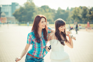 beautiful hipster young women sisters friends dancing listening music  in the city