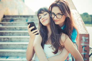 beautiful hipster young women sisters friends using smartphone  in the city