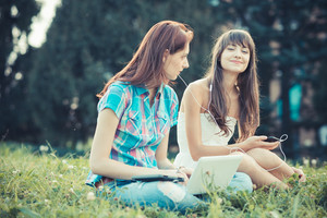 beautiful hipster young women sisters friends using tablet and smartphone in the park