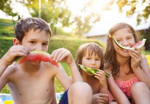 Beautiful kids eating watermelon outside in the garden