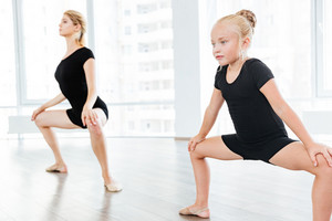 Beautiful little dancer and her dancing teacher doing stretching exercises in a studio