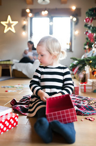 Beautiful little girl at the illuminated and decorated Christmas tree opening her Christmas present.