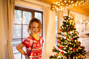 Beautiful little girl decorating Christmas tree tangled in chain of lights.