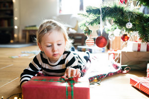 Beautiful little girl lying under the Christmas tree opening her Christmas present.