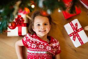 Beautiful little girl under Christmas tree lying among presents.