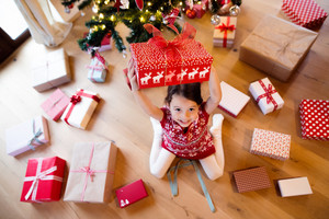 Beautiful little girl under Christmas tree sitting among presents, holding one above her head.