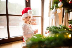 Beautiful little girl with red hat decorating Christmas tree.