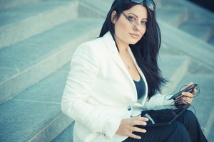 beautiful long black hair elegant business woman using smartphone in the city
