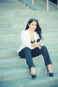 beautiful long black hair elegant business woman using smartphone in the city