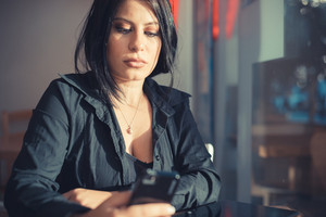 beautiful long black hair elegant business woman using tablet and smartphone in the city