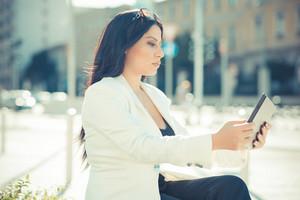 beautiful long black hair elegant business woman using tablet in the city