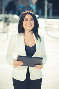 beautiful long black hair elegant business woman using tablet in the city