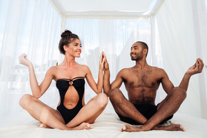 Beautiful multiracial couple mediating together and sitting in lotus position on the beach bed