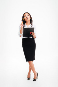 Beautiful pensive asian businesswoman holding clipboard and thinking about something isolated on white background