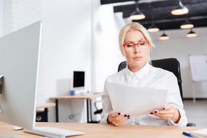 Beautiful pensive mature businesswoman reading papers in office