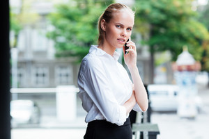 Beautiful pensive young business woman talking on mobile phone outdoors