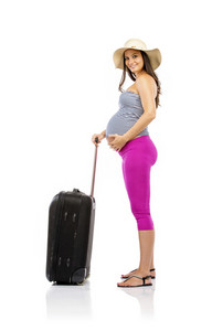 Beautiful pregnant woman in summer clothes and straw hat ready to travel, isolated on white