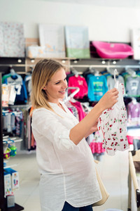 Beautiful pregnant woman in white shirt shopping clothes for her baby