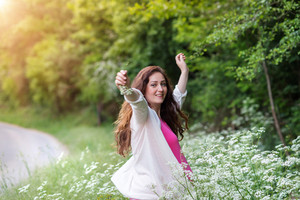 Beautiful pregnant woman wearing pink t-shirt and white cardigan, arms outstretched. Green sunny summer nature.
