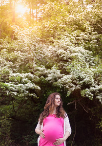 Beautiful pregnant woman wearing pink t-shirt holding her belly. Green sunny summer nature.